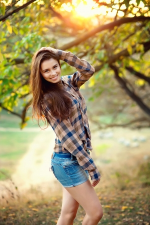 Young girl in denim shorts and a multicolored shirt Stock Photo - 17743207