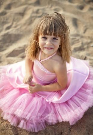 Beautiful little girl in a pink dress walking photo