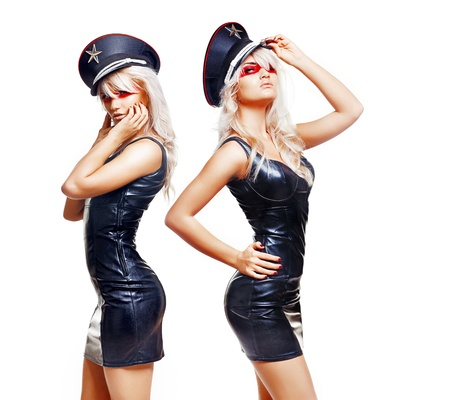 Two sexy twins wearing short black dresses and a peaked caps Stock Photo - 8434044