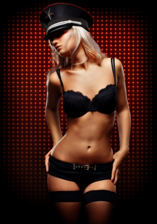 Young sexy woman in front of wall of red bulbs Stock Photo - 8434032