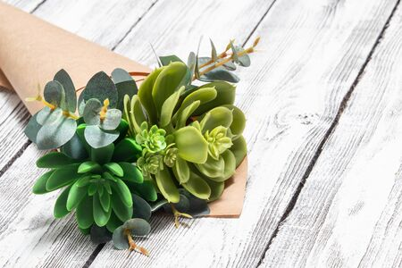 bouquet of succulents in brown craft paper