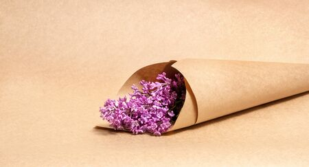 a bouquet of lilac flowers wrapped in brown craft paper