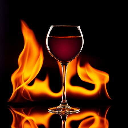 glass of red wine on black with flames