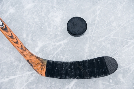 ice hockey puck: ice hockey stick and puck on ice Stock Photo