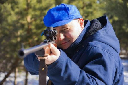 aiming hunter with a blue cap Standard-Bild