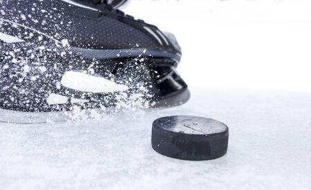 hockey skate with snow splashes and puck Standard-Bild - 134093173