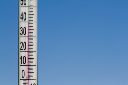 The thermometer in the heat of summer on a background of blue sky. Standard-Bild
