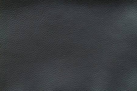 Texture of old crumpled black leather. The dark background.