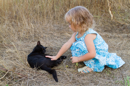 kind of: Young kind girl plays with a black cat. Stock Photo