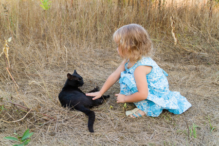 kind: Young kind girl plays with a black cat. Stock Photo