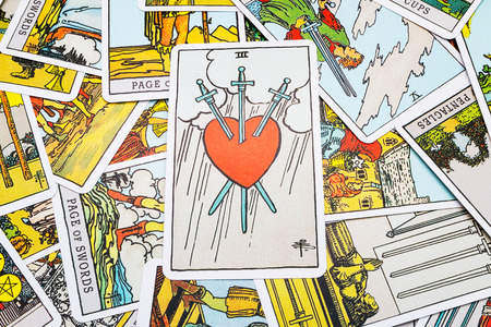 Tarot cards Tarot, the Heart with swords  card in the foreground.