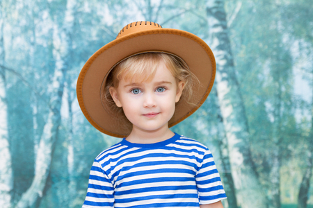 young tree: Little girl playing in cowboy brown hat. Stock Photo
