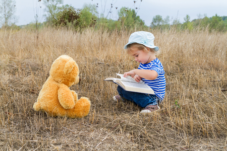 Cute girl reading book Teddy bear on the grass.