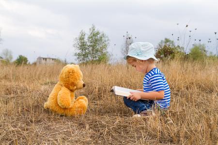 草の上本テディベアを読んでいるかわいい女の子。