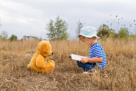 kid reading: Cute girl reading book Teddy bear on the grass.