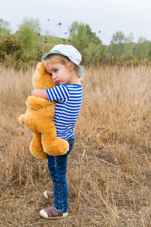 friend hug: Cute little girl standing in the grass hugging a Teddy bear Stock Photo