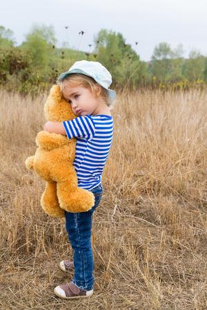 Nettes kleines Mädchen im Gras stehend umarmt einen Teddybären Standard-Bild - 45662445