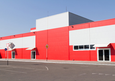 On the facade of a large industrial building made of aluminum panels red.