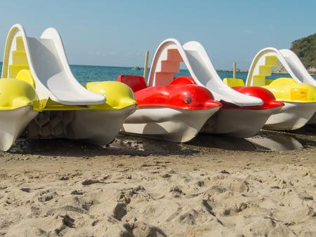 ocean kayak: Catamaranes en forma de delfines de colores en una orilla del mar de arena.