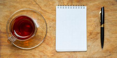 lapiz y papel: Pequeño cuaderno con una taza de té, se pega sobre un fondo de madera rústica. La vista desde la parte superior.