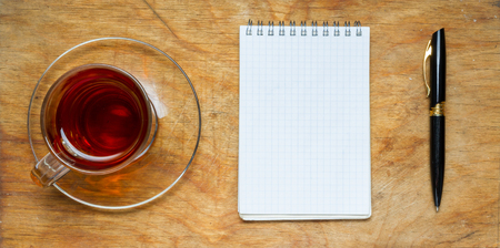 pencil and paper: Small notebook with a Cup of tea, stick on a rustic wood background. The view from the top. Stock Photo