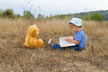 book concept: Cute girl reading book with Teddy bear on the grass.