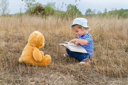 Cute girl reading book with Teddy bear on the grass.