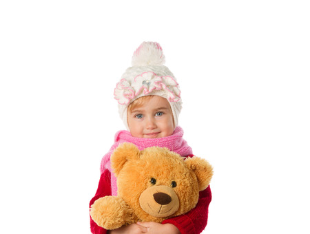 catarrh: Little girl in warm hat and a red sweater with Teddy bear isolated on a white background.