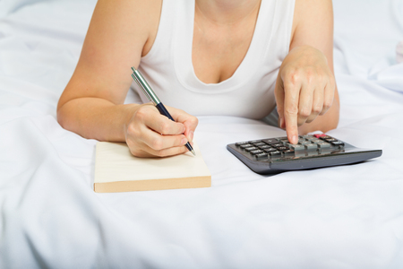 budget: young woman on the bed with a notebook and calculator.Credit, mortgage. Family budget.