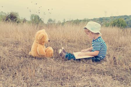 storytelling: Cute girl reading book Teddy bear on the grass.