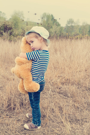 Cute little girl standing in the grass hugging a Teddy bear Stock Photo