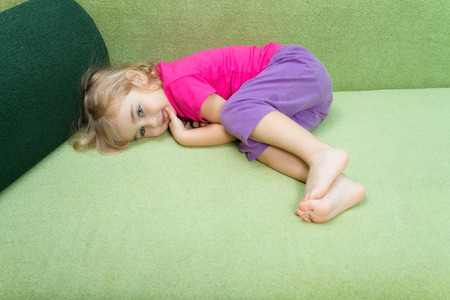 green couch: Little girl lies on a green couch.