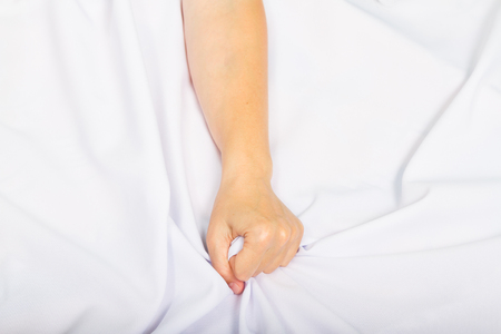 female sex: Female hand pulling white sheets in ecstasy, orgasm. Stock Photo