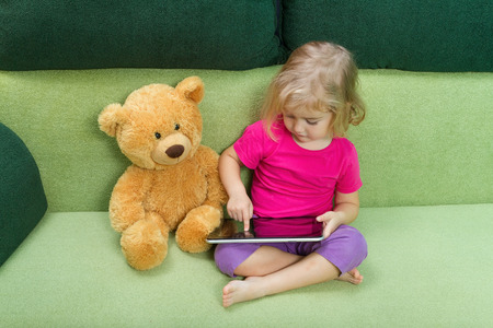 Little girl with Teddy bear, and a tablet. Sitting on a green couch.