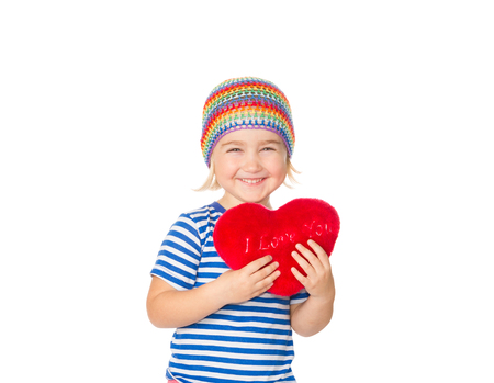 baby love: Little girl holding a red heart toy. Isolated on a white background.