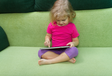 playing on divan: Cute little girl using tablet computer sitting on a green couch.