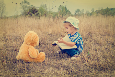 kids reading book: Cute girl reading book Teddy bear on the grass.