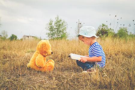 personas leyendo: Cute girl reading book Teddy bear on the grass.