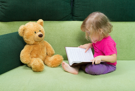 green couch: Little girl reading a book Teddy bear sitting on a green couch. Stock Photo