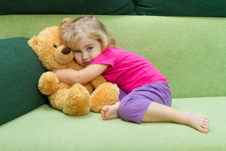 naptime: Little girl hugging Teddy bear on a green soft couch.