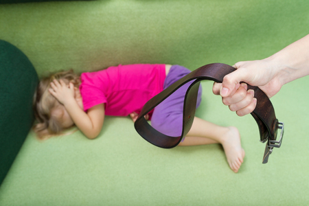 leather belt: Family violence and aggression concept - furious angry man raised punishment hand holding leather belt over scared or terrified child Stock Photo