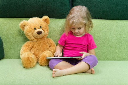 green couch: Little girl with Teddy bear, and a tablet. Sitting on a green couch.