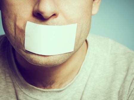 Caucasian man with duct tape on mouth, white . Conceptual image.