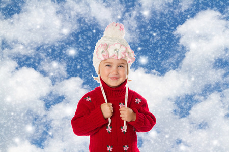 ponytails: Little girl with ponytails in a warm hat and red sweater on the background of sky and snow. Stock Photo