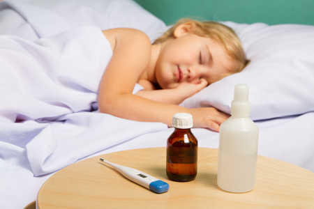 cold cure: Sick little girl in bed.Virus, flu, cold, fever.( focus on the cure) Stock Photo