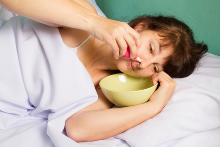 female in douche: Woman lying on the bed, washes the nose. Stock Photo