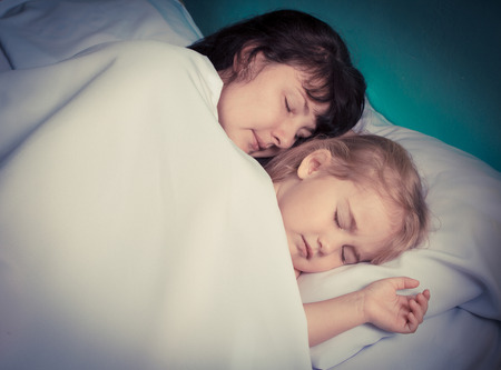 three year old: Mother and her three year old daughter sleep on the bed at home