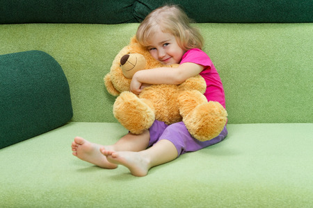 playing on divan: Little girl hugging Teddy bear on a green soft couch.