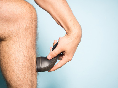 shave: Close up of young Caucasian man shaving hair from legs