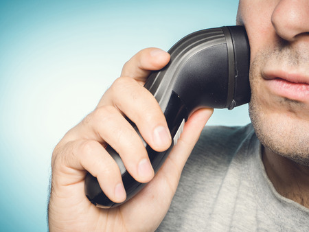 electric shaver: Caucasian man shaving his beard off with an electric shaver Stock Photo